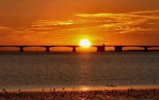 De zon zakt weg achter de Zeelandbrug (foto genomen vanaf de hoek van Ouwerkerk)